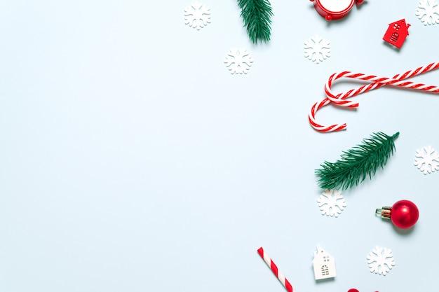 Disposizione piana di ramoscelli di abete, palle di natale, bastoncino di zucchero, casa e fiocchi di neve