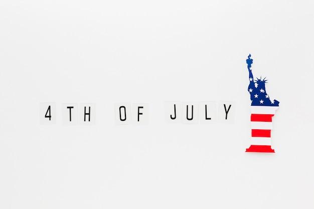 Disposizione piana della statua della libertà con la bandiera americana per la festa dell'indipendenza