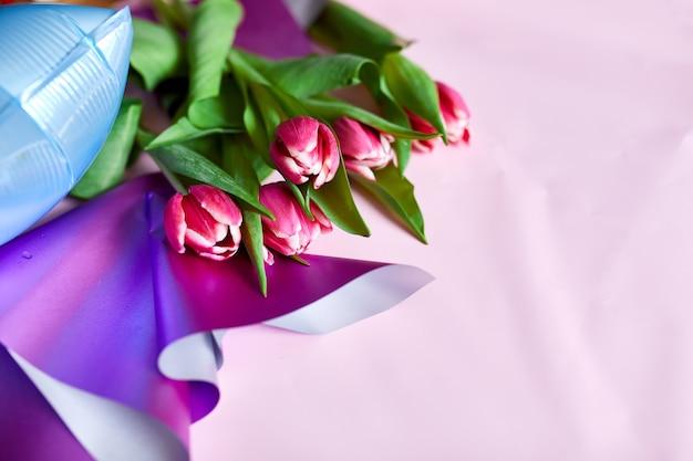 Stile piatto di palloncini colorati con decorazione floreale di tulipani su sfondo rosa. compleanno, vacanza o concetto di festa, copia spazio per il testo.