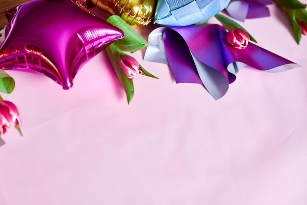 Stile piatto di palloncini colorati con decorazione floreale di tulipani su sfondo rosa.