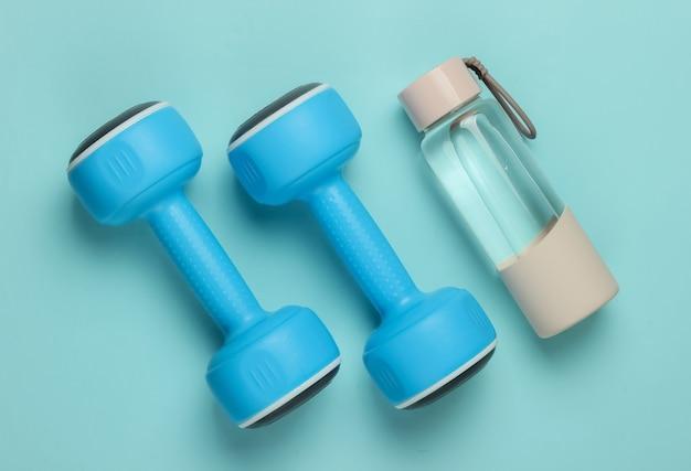 Concetto di stile piatto laici di stile di vita sano, sport e fitness. manubri, bottiglia d'acqua su sfondo blu pastello. vista dall'alto
