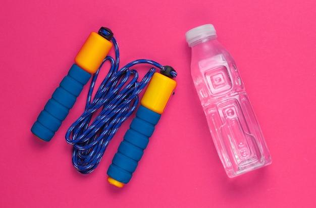 Concetto di sport in stile piatto laici. corda per saltare, bottiglia d'acqua. attrezzature sportive sul rosa