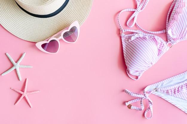 Disposizione piatta di articoli estivi con bikini a strisce di colore rosa e bianco, corallo a forma di stella marina