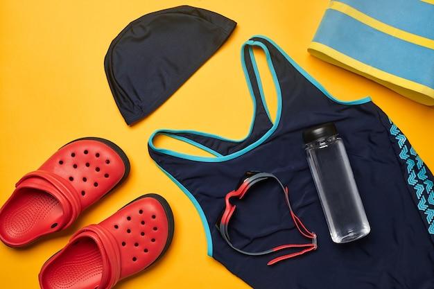 Accessori per piscina estivi piatti su uno sfondo giallo abbigliamento da spiaggia colorato
