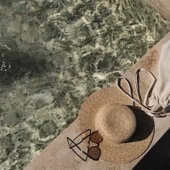 Disposizione piatta di occhiali da sole e cappello di paglia sul lato della piscina in marmo con acqua blu chiara con riflessi di ombra di luce solare delle onde
