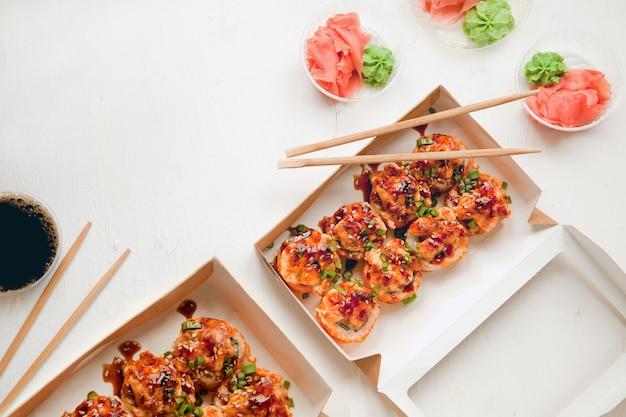 Rotoli di sushi piatti con zenzero e wasabi al forno sushi con salmone su confezione di carta