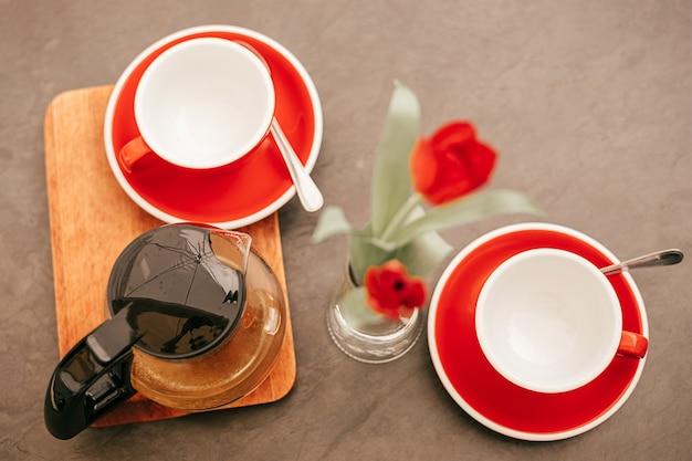 Piatto disteso, teiera con tè e due tazze vuote rosse su un tavolo di legno.