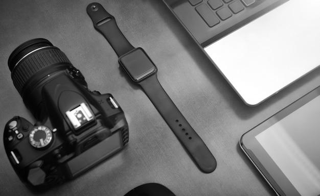 Disposizione piana degli oggetti techno per il lavoratore moderno con il telefono cellulare dello smartwatch e la macchina fotografica del dslr sulla tavola di legno.