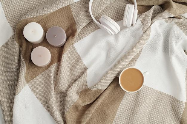 Lay piatto di tre piccole candele aromatiche, cuffie bianche e tazza di cappuccino fresco su lino a scacchi o plaid di cotone