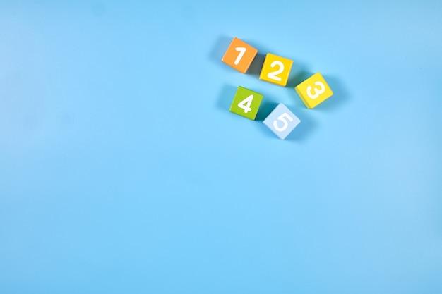Vista dall'alto piatto laico di cubi numerici colorati luminosi con numeri su mattoni di legno su colore blu