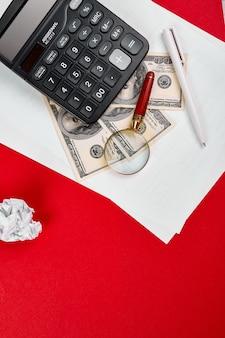 Vista piana laico o superiore della calcolatrice, dollari di denaro e blocco note del libro bianco su sfondo rosso, affari, finanza, risparmio, investimento, tasse o concetto di contabilità