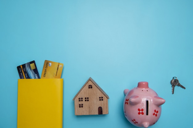 Vista piana, vista dall'alto del concetto di costruzione o business immobiliare te piccola casa in legno e carta di credito per l'acquisto di proprietà, casa, strumenti di costruzione sulla parete blu
