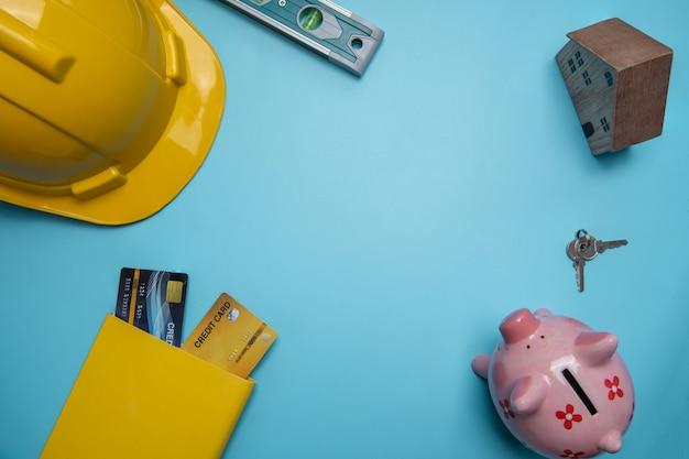 Vista piana laico, vista dall'alto di costruzione o business immobiliare concetto con casco giallo e piccola casa in legno e carta di credito per l'acquisto di proprietà, casa, strumenti di costruzione sulla parete blu