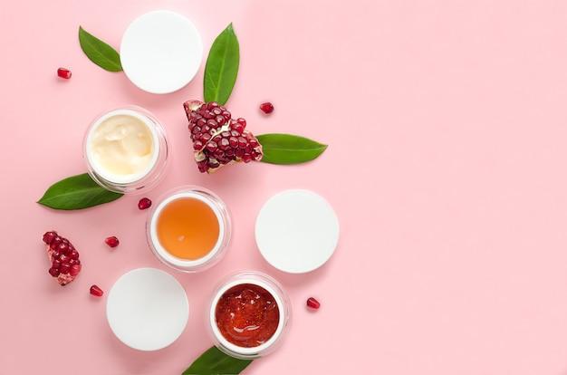Prodotto cosmetico disteso a vista dall'alto per la cura della pelle con estratto di melograno. cosmetici con acidi della frutta su sfondo rosa. vuoto, sagoma, copia spazio, testo. concetto di bellezza