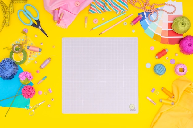 Scrivania da tavolo piatta, vista dall'alto. area di lavoro con tappetino per il taglio, forbici, stoffa, carta, nastro adesivo, matite, etichette, pulsanti sul giallo