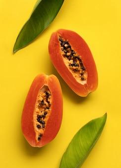 Composizione creativa di vista dall'alto laica piatta fatta di papaia e foglie.