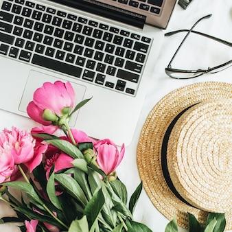 Scrivania da ufficio per donna alla moda con vista dall'alto piatta con fiori di peonia, laptop su sfondo bianco