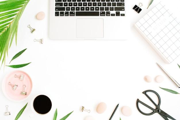 Cornice piatta, vista dall'alto della scrivania del tavolo da ufficio. area di lavoro con notebook, laptop, ramo di palma, tazza di caffè, forbici e clip su sfondo bianco.