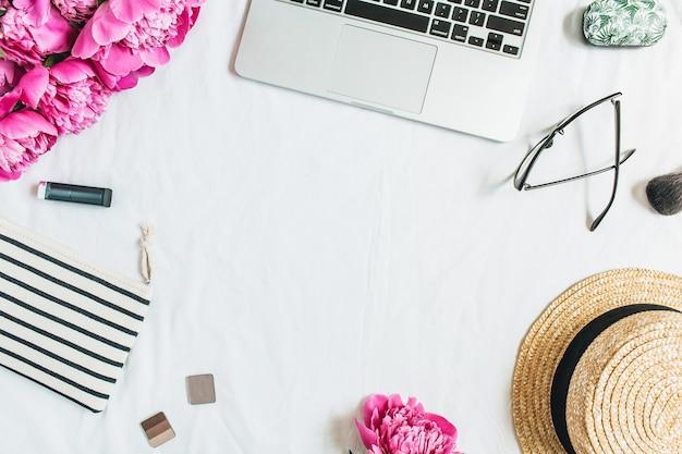Cornice piatta, vista dall'alto dell'area di lavoro della scrivania da ufficio delle donne con laptop, bouquet di fiori di peonia rosa, cosmetici, occhiali, cappello di paglia su sfondo bianco