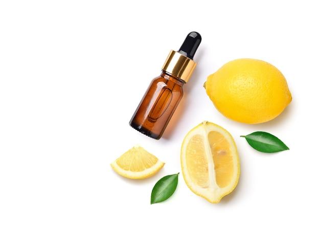 Lay piatto (vista dall'alto) di olio essenziale di limone in flacone contagocce con fette e foglie su bianco.