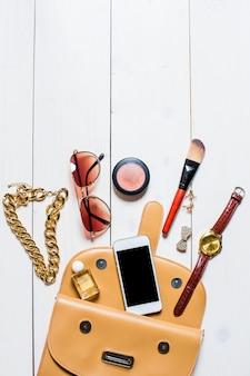 Disposizione piatta, vista dall'alto, cosmetici finti e accessori da donna caduti dalla borsa beige su sfondo bianco. telefono, orologi, occhiali da sole, profumi