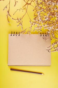 Notebook con vista dall'alto piatto laico, note con fiori famiglia futura, casa, obiettivi di vita e piano o avvio di una nuova attività, concetto