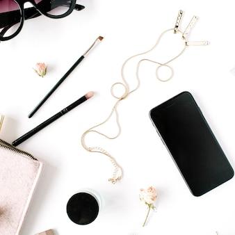 Struttura della scrivania del tavolo da ufficio con vista dall'alto e piatta. area di lavoro femminile della scrivania con frizione, cosmetici, telefono, occhiali da sole, boccioli di rosa rossetto su priorità bassa bianca.