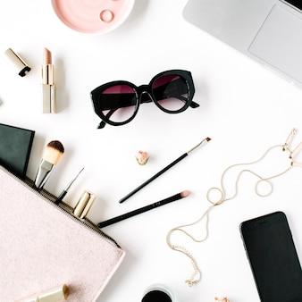 Struttura della scrivania del tavolo da ufficio con vista dall'alto e piatta. area di lavoro femminile della scrivania con laptop, frizione, cosmetici, telefono, occhiali da sole, boccioli di rosa rossetto su priorità bassa bianca.
