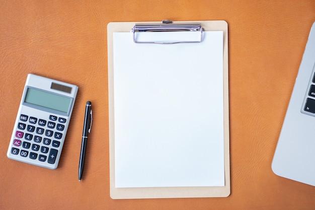Scrivania da ufficio piatta, vista dall'alto, area di lavoro con calcolatrice, penna, laptop, appunti vuoti su fondo in pelle.