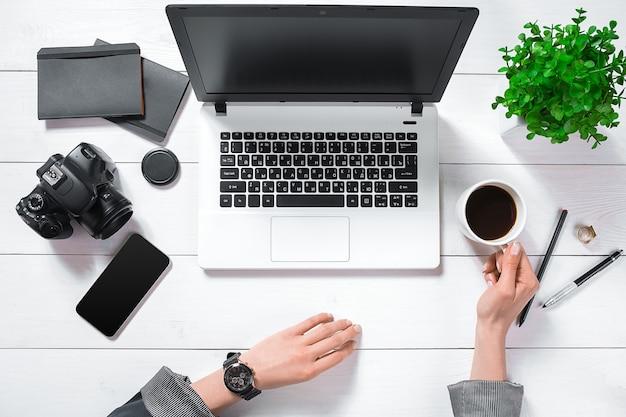 Scrivania da ufficio piatta, vista dall'alto. area di lavoro con le mani della ragazza, laptop, fiore verde in una pentola, diario nero, tazza da caffè su sfondo bianco.