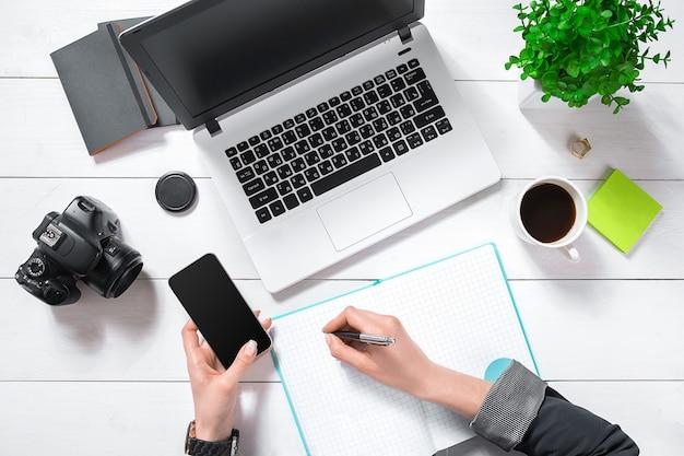 Scrivania da ufficio piatta, vista dall'alto. area di lavoro con le mani della ragazza, laptop, fiore verde in un vaso, diario di menta, tazza da caffè su sfondo bianco.