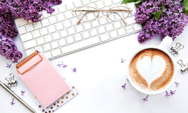 Tavolo da ufficio piatto con vista dall'alto. area di lavoro con tastiera, fiori lilla e articoli per ufficio su sfondo bianco.