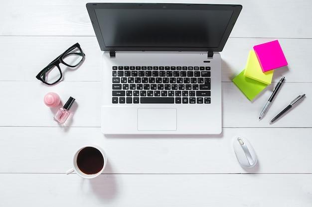 Scrivania da ufficio piatta, vista dall'alto. area di lavoro con laptop, fiore verde in un vaso, diario di menta su sfondo bianco.