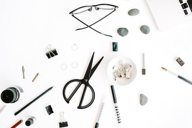 Scrivania da ufficio piatta, vista dall'alto. area di lavoro con laptop, forbici, occhiali, penna su sfondo bianco.