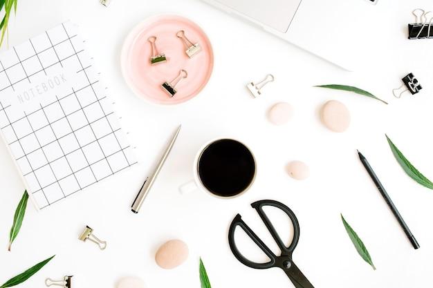Scrivania da ufficio piatta, vista dall'alto. area di lavoro con notebook, laptop, ramo di palma, tazza di caffè, forbici e clip su sfondo bianco.