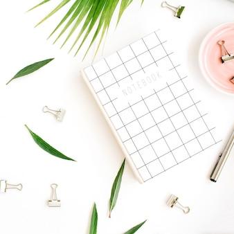 Scrivania da ufficio piatta, vista dall'alto. area di lavoro con notebook, ramo di palma e clip su sfondo bianco.