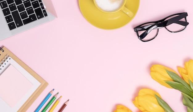 Scrivania da ufficio piatta, vista dall'alto. area di lavoro con pennello, laptop, bouquet di fiori lilla, bobina con nastro beige e blu, diario di menta su sfondo rosa.