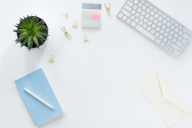 Tavolo da ufficio piatto con vista dall'alto. area di lavoro con pennello, laptop, bouquet di fiori lilla, bobina con nastro beige e blu, diario di menta su sfondo bianco.