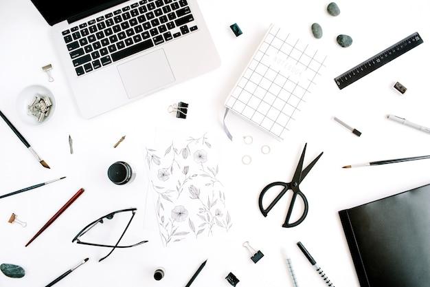 Scrivania da ufficio piatta, vista dall'alto. area di lavoro con pittura, notebook, laptop, forbici, occhiali, penna su sfondo bianco.