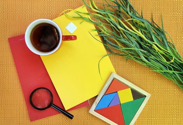 Foto esterna piatta vista dall'alto con lente d'ingrandimento per tazza da tè e taccuini rossi e gialli brillanti e tangram