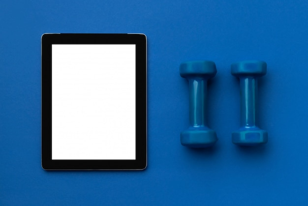Vista dall'alto piatto laico del tablet con attrezzature sportive su sfondo blu classico. concetto di fitness online stile di vita sano