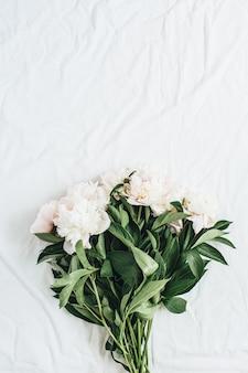 Vista dall'alto piatta del bouquet di fiori di peonie bianche su sfondo bianco coperta blanket
