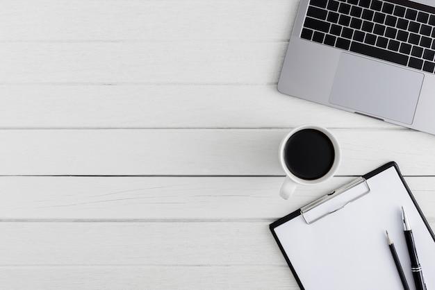 Scrivania da ufficio in legno con vista piana e dall'alto. area di lavoro con appunti in bianco, laptop, penna, forniture per ufficio tazza di caffè con spazio coppy sul fondo della tavola in legno bianco