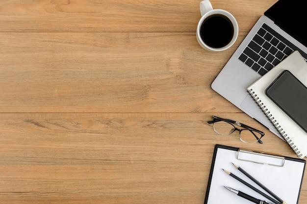 Scrivania da ufficio in legno con vista piana e dall'alto. area di lavoro con appunti in bianco, laptop, smartphone, penna, forniture per ufficio tazza di caffè con spazio coppy sul fondo della tavola in legno