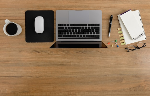 Scrivania da ufficio in legno con vista piana e dall'alto. area di lavoro con taccuino in bianco, laptop, mouse, penna, occhiali, forniture per ufficio tazza di caffè con spazio coppy sul fondo della tavola in legno