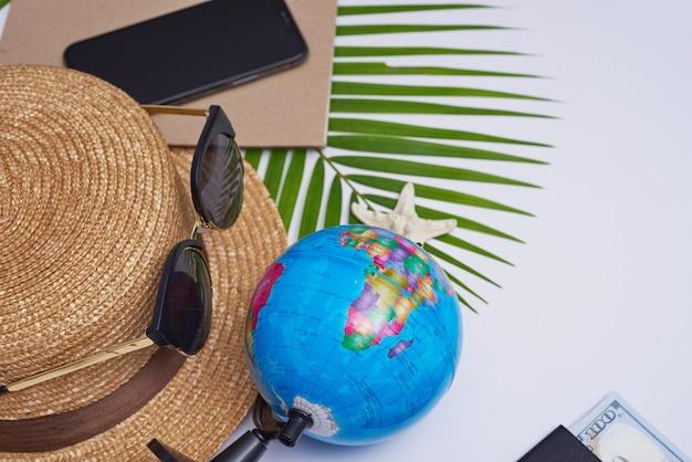 Accessori da viaggio piatti laici su superficie bianca con foglia di palma, macchina fotografica, cappello, passaporti, soldi, globo, libro, telefono, mappa e occhiali da sole. vista dall'alto, viaggio o concetto di vacanza