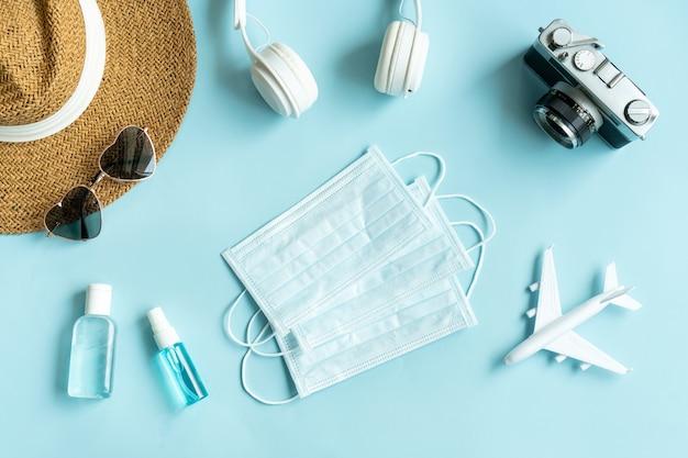Disposizione piatta di accessori per viaggiatori e articoli medici sul colore blu