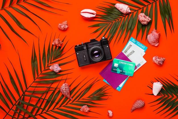 Accessori per viaggiatori piatti laici con foglia di palma, conchiglie, fotocamera, passaporto, denaro e biglietto aereo