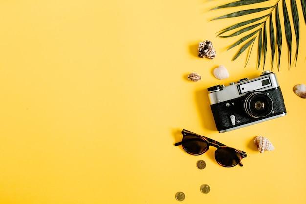 Accessori per viaggiatori piatti laici su giallo con foglia di palma, fotocamera e occhiali da sole