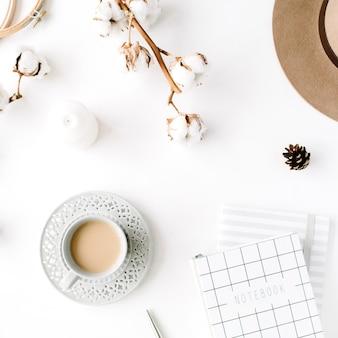 Disposizione di accessori femminili creativi alla moda piatti laici con caffè, ramo di cotone e diario. cappello, ramo di cotone, taccuino, tazza di caffè, cono di abete, clip dorate su sfondo bianco.